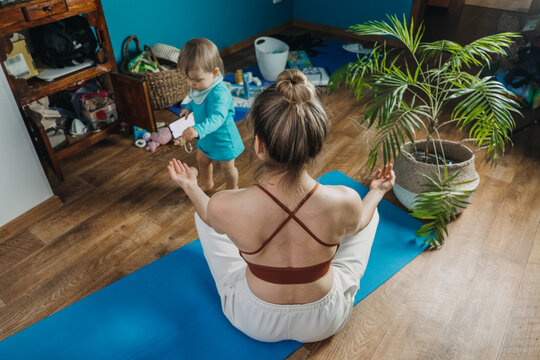 Young mother sitting on the floor, enjoy meditation do yoga exercise at home with his little daughter baby girl. Mental health, self care, No stress, healthy habit, appeasement, anxiety relief concept