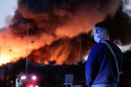 A man wears a face mask near a fire in a scrap metal recycling plant of Deacero company in Guadalupe, on the outskirts of Monterrey