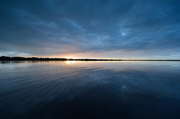 Winter cloudscape reflected in tranquil water of Coot Bay in Everglades National Park in late afternoon.