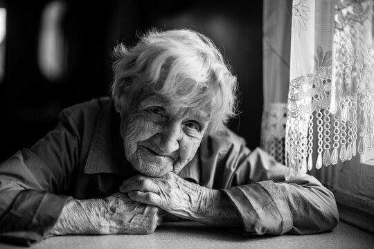 An old woman in the house sitting at the table. Black and white photo.