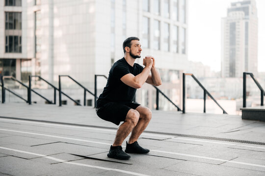Fit man training air squat exercise. Fit male exercising crossfit outside. Young handsome caucasian male fitness model and instructor outdoors. Black sportswear. Sport in big city concept.