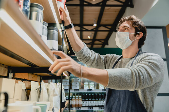 Young attractive waiter in medical mask against coronavirus taking glasses from the shelf in coffee shop