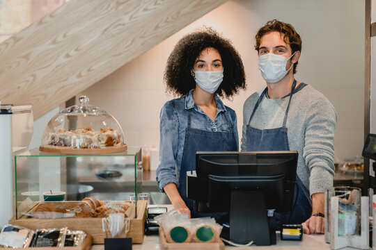 Two cafeteria staff standing at cafe counter in medical masks against Covid 19 in small coffee shop