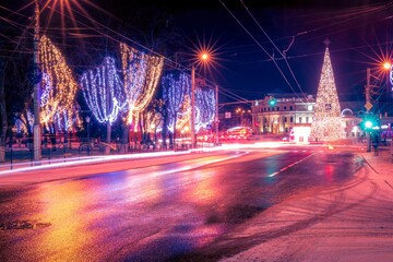 Night city with Christmas decorations, spruce and traces of headlights of moving cars, reflected in the wet road.