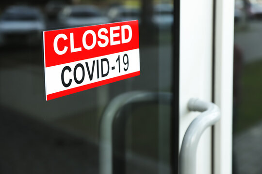 "Red sign with words ""Closed Covid-19"" hanging on glass door"