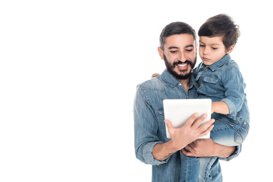 Hispanic man holding grandson and digital tablet isolated on white, two generations of men