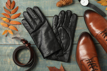 Flat lay composition with stylish black leather gloves and autumn decor on blue wooden table Wall mural