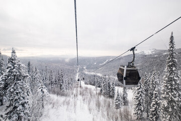 Gondola lift in the ski resort on snow covered slop, winter trees, mountains landscape