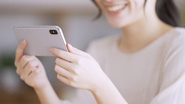 スマートフォンで動画を観る若い女性