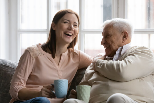 Family members of two generations grown daughter and mature father having fun enjoy tea talk on cozy couch. Attentive young lady caregiver social worker visit support care for glad elderly man patient