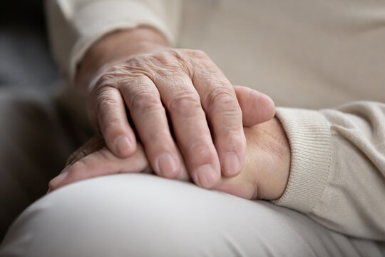 Close up of elderly male sitting alone keeping wrinkled work-weary hands folded on knees. Retired old man think ponder of loneliness need attention care. Senior person waiting for doctor appointment
