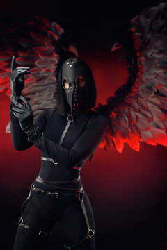 a woman wearing a plague doctor mask with leather straps and black wings on a dark red background