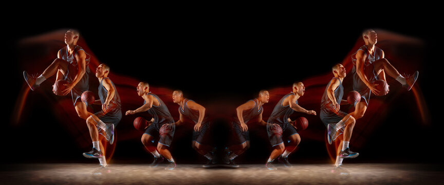 Young purposeful basketball player training in action on black background with fire flames. Mirror, strobe light effect, reflection. Concept of sport, movement, energy and dynamic, healthy lifestyle.