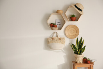 Fototapeta Hexagon wooden shelves with beautiful plants and accessories on light wall. Space for text obraz