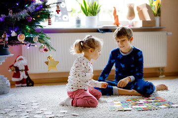 Two little chilren, cute toddler girl and school kid boy playing together card game by decorated Christmas tree. Happy healthy siblings, brother and sister having fun together. Family celebrating xmas Wall mural
