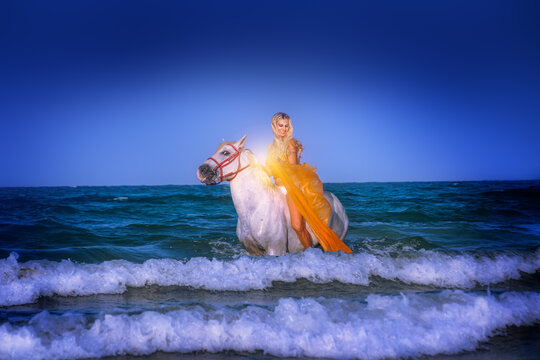 Pretty blond female model horse riding on beach and in the ocean. Horse back riding.