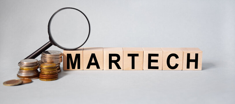 finance, inscription on the cubes, the word MARTECH on cubes of wooden texture on a light background, together with coins and a magnifying glass.
