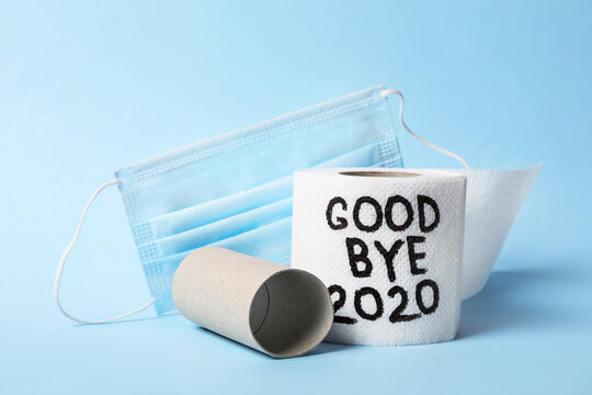 Toilet paper roll with text Goodbye 2020 and medical face mask on light blue background