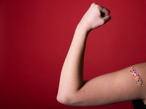 Female arm flexing bicep and making a fist wearing a bandage after receiving a Covid-19 Coronavirus vaccine injection