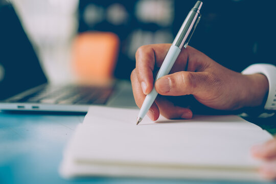Woman hand writing down in small white memo notebook for take a note not to forget or to do list.