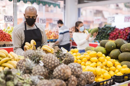 Portrait of latino-american worker in mask in supermarket with pineapples during coronavirus pneumonia outbreak