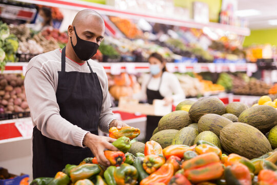 Supermarket employee in protective mask lays out bell peppers on the shelves