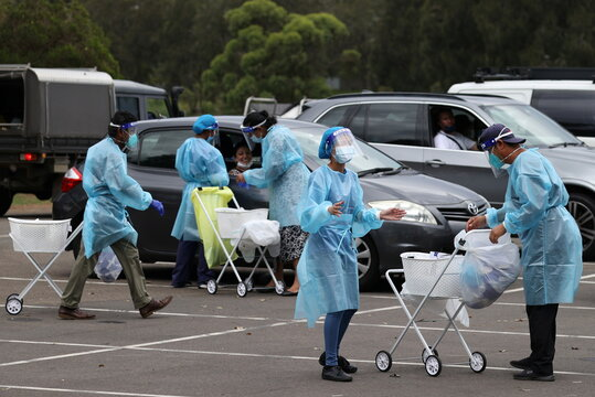 Medical professionals work at a drive-through coronavirus disease testing clinic in Sydney