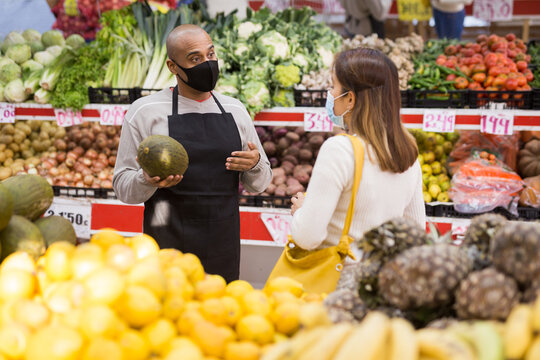 Store employee helping girl choosing fruit in supermarket. People in medical masks during COVID-19