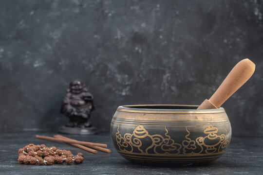 Singing bowl with wooden stick and tibetan beaded rosary on gray background