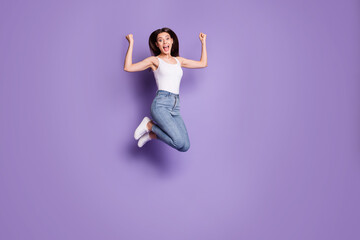 Full size photo of triumphant brown haired girl jump up wear white tank-top jeans discount raise fists isolated on purple color background Wall mural