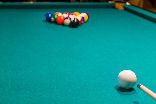 Sports game of billiards on a green cloth. Multi-colored billiard balls with numbers on a pool table