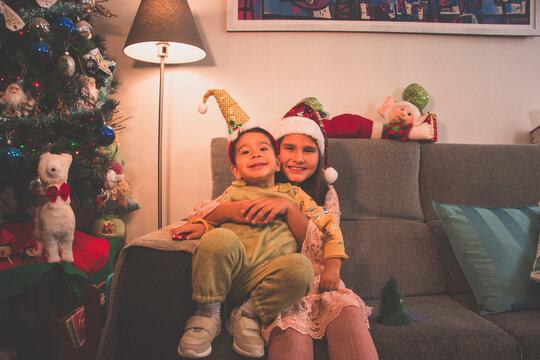Niño y niña con gorros navideños. Hermanos abrazados en el sofá de su casa junto al árbol de Navidad