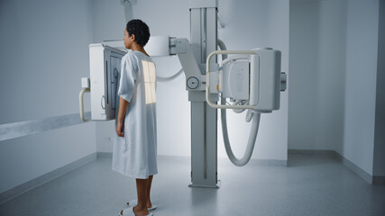 Hospital Radiology Room: Beautiful Latin Woman Standing Next to X-Ray Machine While it Scans Back....