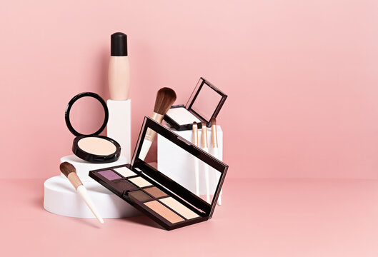 Make up products prsented on white podiums on pink pastel background.