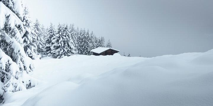 Panoramabild einer Winterlandschaft mit Skihütte am Wald