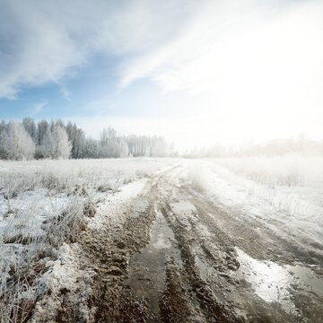 An old rural road covered with ice and snow after a blizzard. Field and forest. Trees in a hoarfrost. Russia. Concept landscape. Off-road, winter tires, logistics, dangerous driving, remote village