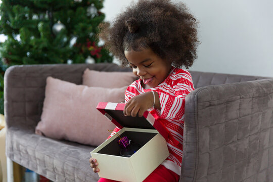 Merry Christmas and Happy Holidays. Cheerful African American little smiling girl opening Christmas gift box or presents gift, sitting on sofa at home, Christmas tree background. Christmas time