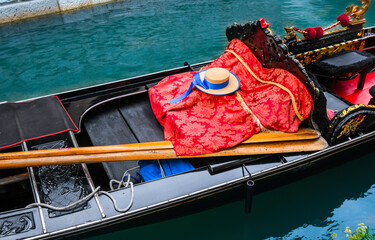 Close up of an empty Venetian gondola with hat, oars and blanket visible in Venice, Italy