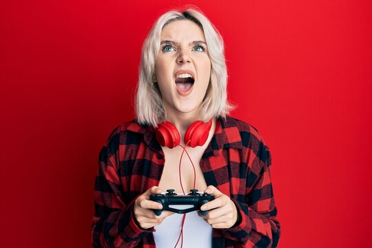 Young blonde girl playing video game holding controller angry and mad screaming frustrated and furious, shouting with anger looking up.