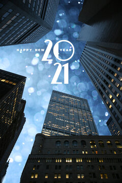 Happy New 2021 year text in beautiful winter snowfall sky seen through city skyscrapers skyline in downtown Manhattan, New York.