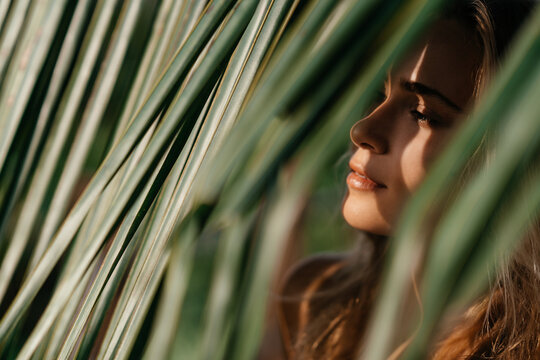 portrait of tender woman looking out of palm leaf Bali Indonesia