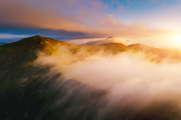 Wall Mural - Splendid view from a drone flying over the morning alpine mountains.