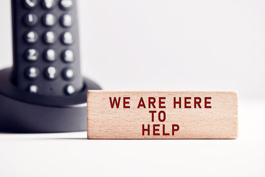 The word we are here to help on wooden block with telephone background. Business concept for customer support.