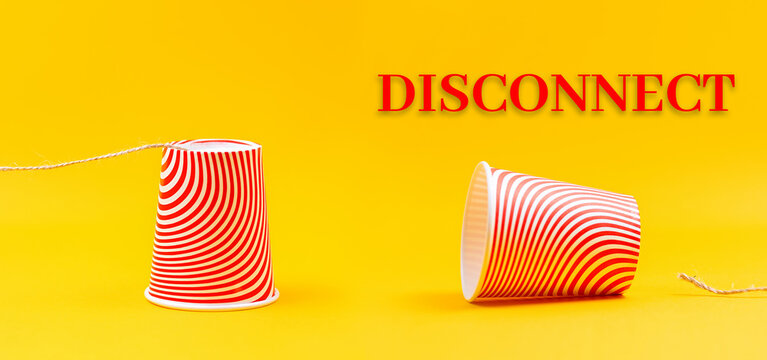 Two cardboard red cups with strings lying apart. Children's homemade toy walkie-talkie. Yellow background. Banner. The concept of communication interruption and disconnection