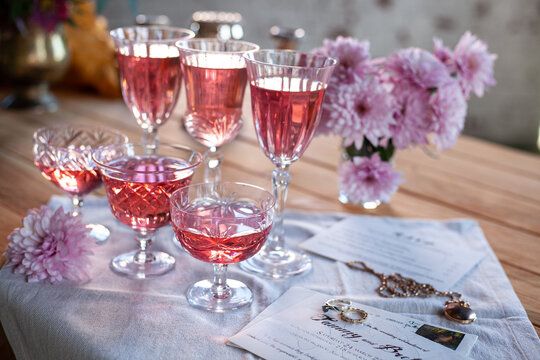 crystal glasses with rose wine, flowers on a wooden table. Wedding decoration