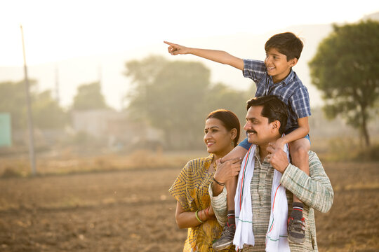 Happy rural Indian family on agricultural field