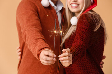 Happy young couple with Christmas sparklers on color background, closeup