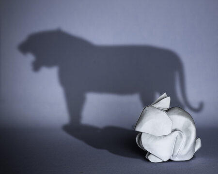 Concept of hidden potential. A paper figure of a rabbit that fills the shadow of a tiger. 3D illustration