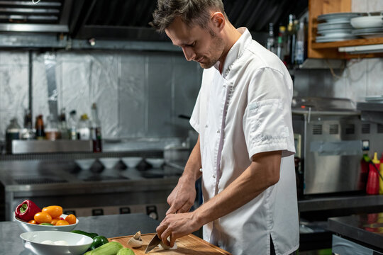 Young professional chef of modern restaurant in uniform cutting vegetables
