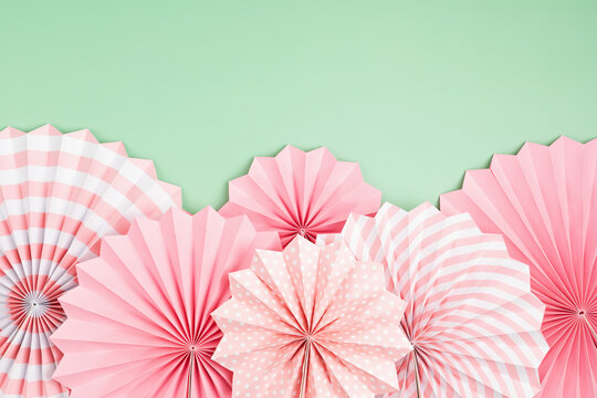 Festive party background with pink paper circle fans over pastel background. Festival, birthday, baby shower decoration
